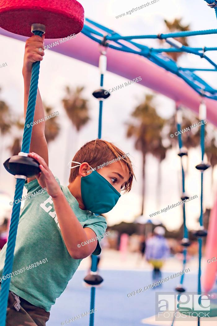 Stock Photo: Boy wearing a mask playing alone at a playground - hanging.