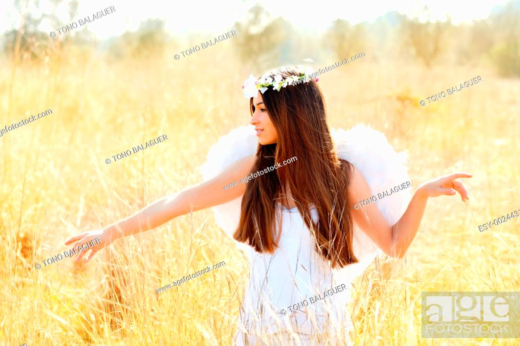 Stock Photo: Angel etchnic woman in golden field with feather white wings and flowers crown.