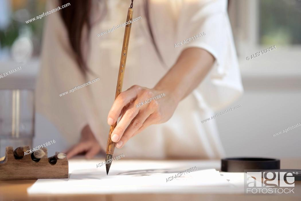 Imagen: Artistic closeup of a woman Japanese sumi-e artist hand with a brush painting on rice paper in her studio wearing white.