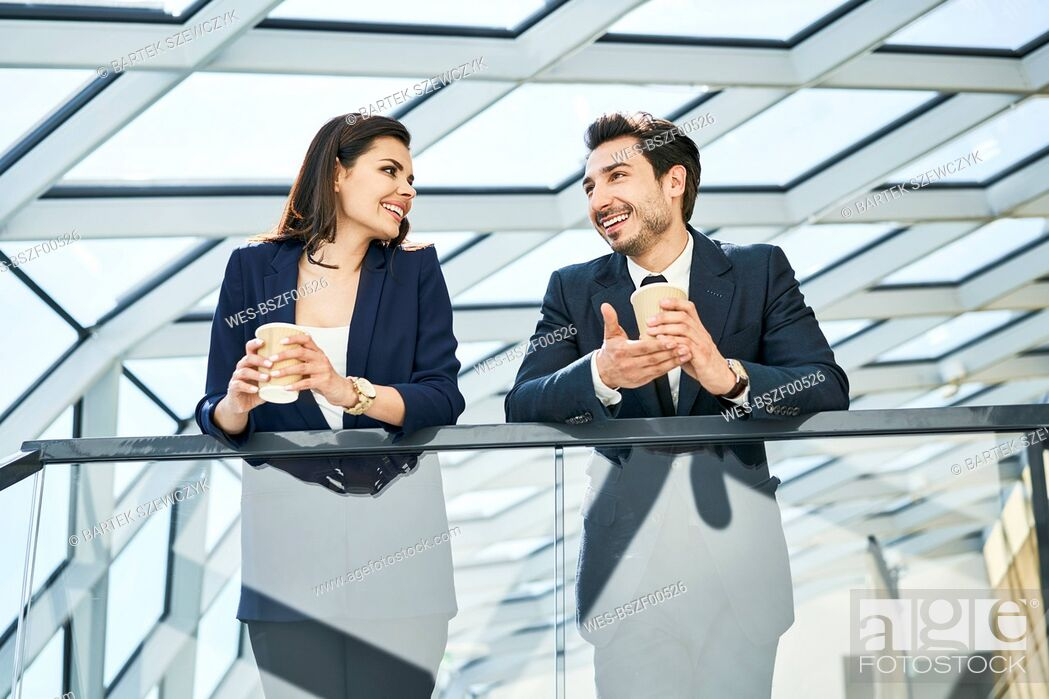 Stock Photo: Smiling businesswoman and businessman having a coffee break in modern office.