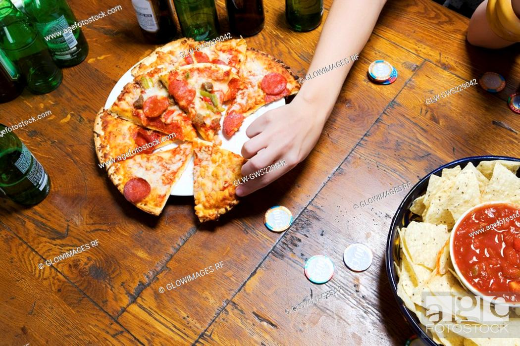 Stock Photo: High angle view of a person's hand picking up a pizza slice.