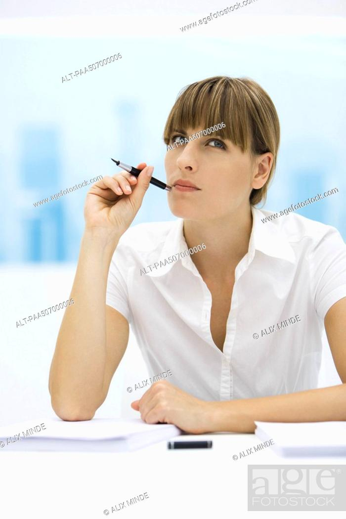 Stock Photo: Woman looking up and holding pen up to her cheek.