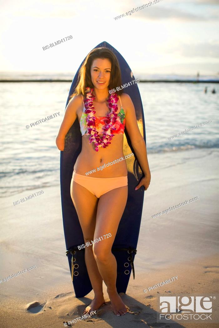 Imagen: Mixed race amputee holding surfboard on beach.
