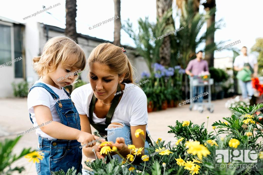 Stock Photo: Female worker of a garden center showing flowers to a little girl.