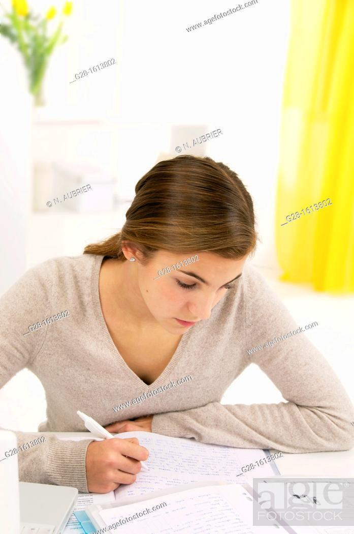 Stock Photo: teenage girl doing her homework at home.