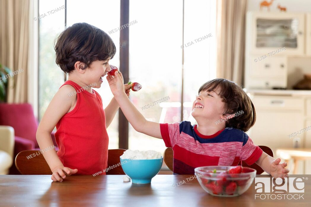 Stock Photo: Laughing twin brothers playing with strawberries at home.