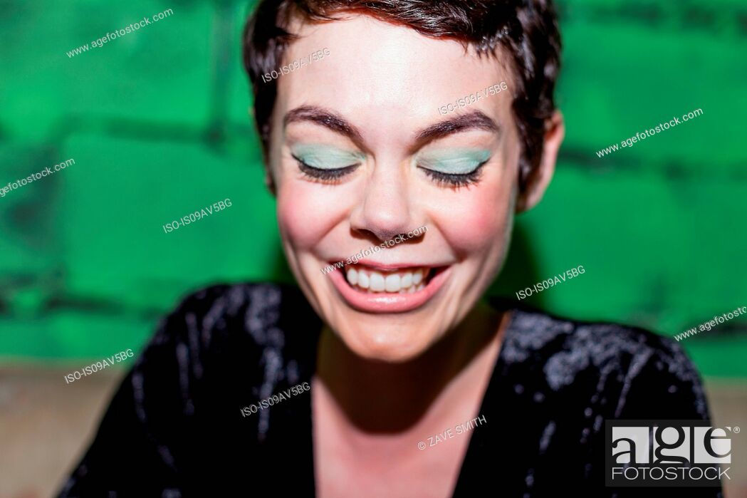 Stock Photo: Mid adult woman with green eye-shadow, smiling.