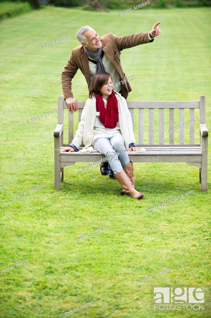 Stock Photo: Man sitting with his daughter on a bench and pointing in a park.