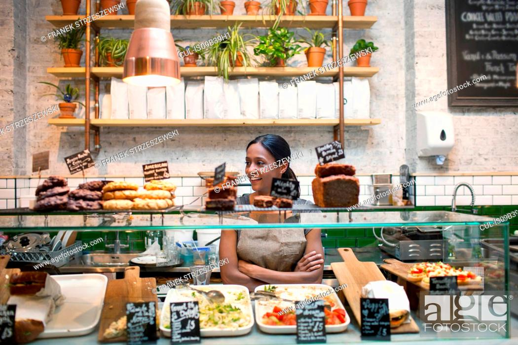 Stock Photo: Waitress standing behind cafe display cabinet.