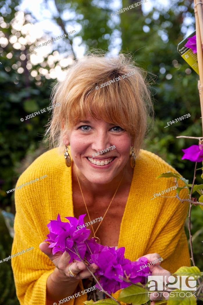 Stock Photo: A pretty 42 year old blond woman smiling at the camera holding flowers of a Bougainvillea plant.