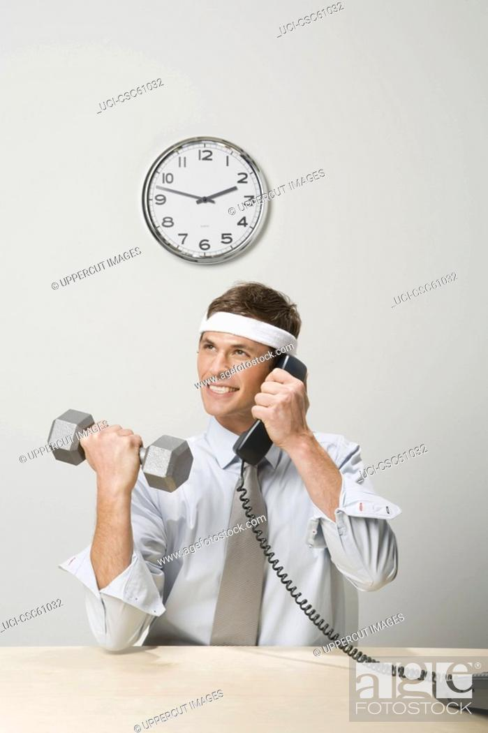 Stock Photo: Businessman lifting weight while talking on telephone.