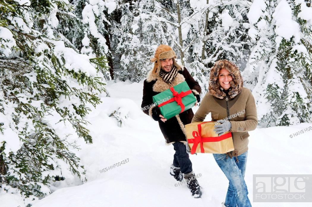 Stock Photo: Austria, Salzburg County, Couple holding christmas gift and walking in snow.
