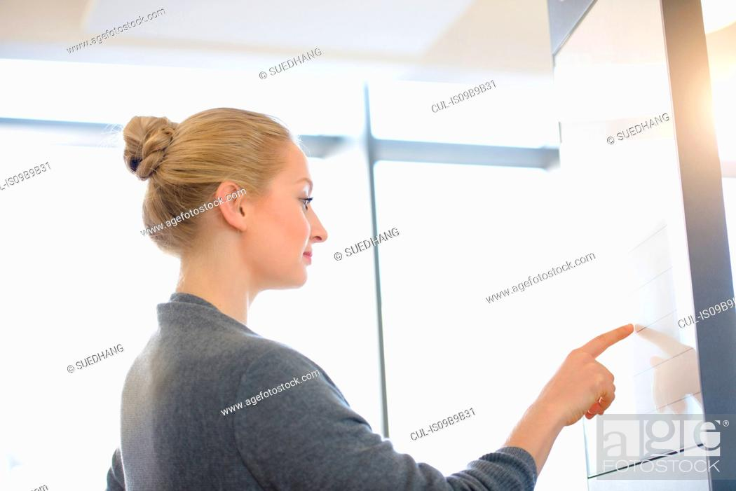 Stock Photo: Young businesswoman in office pointing at board.