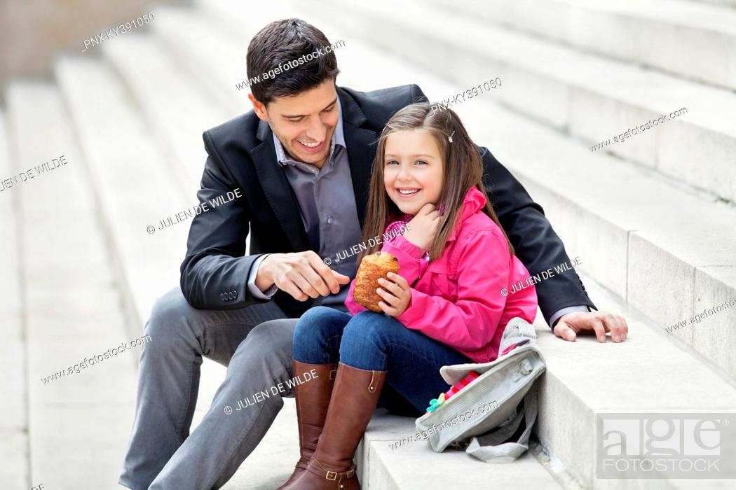 Stock Photo: Man sitting with his daughter eating pain au chocolat.