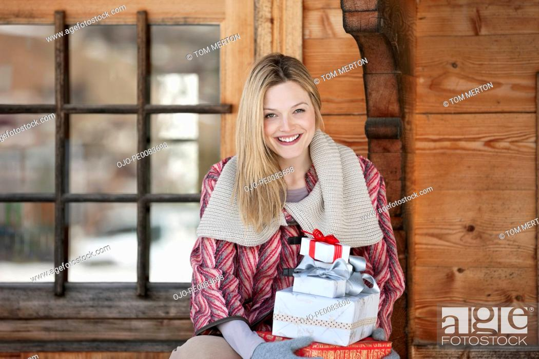Stock Photo: Portrait of smiling woman holding Christmas gifts on cabin porch.