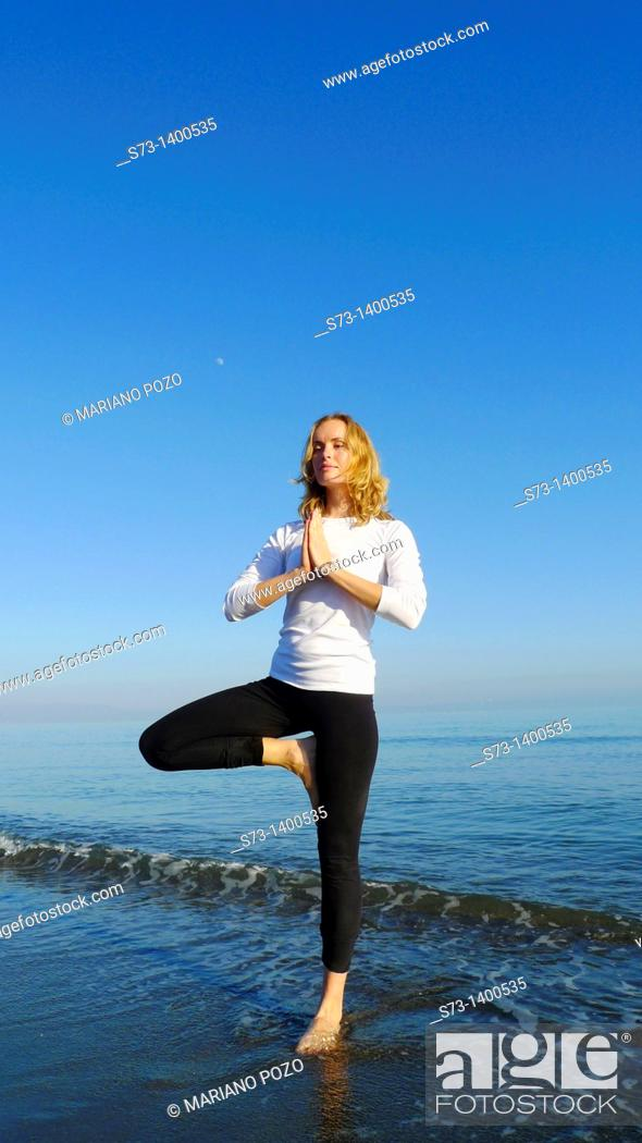 Stock Photo: Young woman doing yoga in a mediterranean beach.