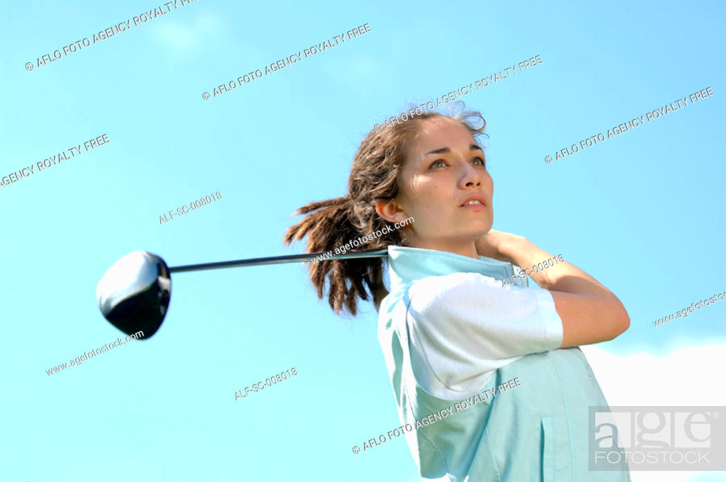 Stock Photo: Portrait of a young woman holding a golf club.