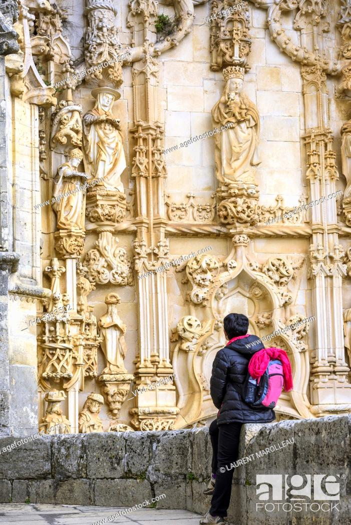 Imagen: (Model Release) Woman watching the Tympanum (with figures of the Christian religion), Portal of the Manueline church, Convent of Christ in Tomar.