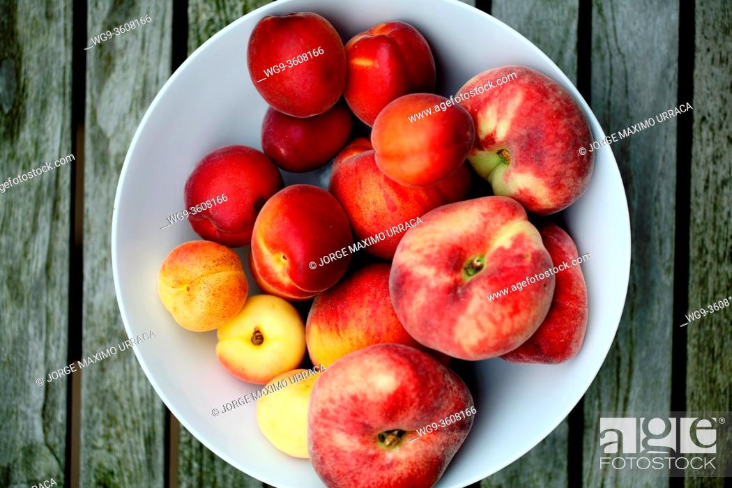 Stock Photo: Summer fruits in white bowl on wooden table view from above.