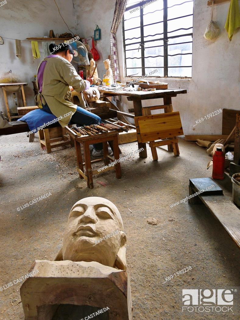 Stock Photo: Worker sculpting and wood carving at his studio. Suzhou. China.