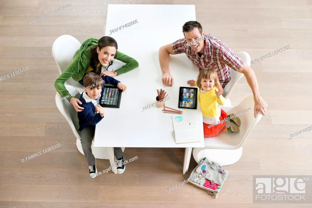 Stock Photo: High angle view of couple with their children at study table.