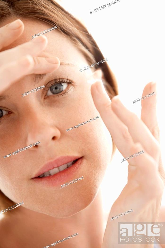 Stock Photo: Woman Inserting Contact Lens close up of face.