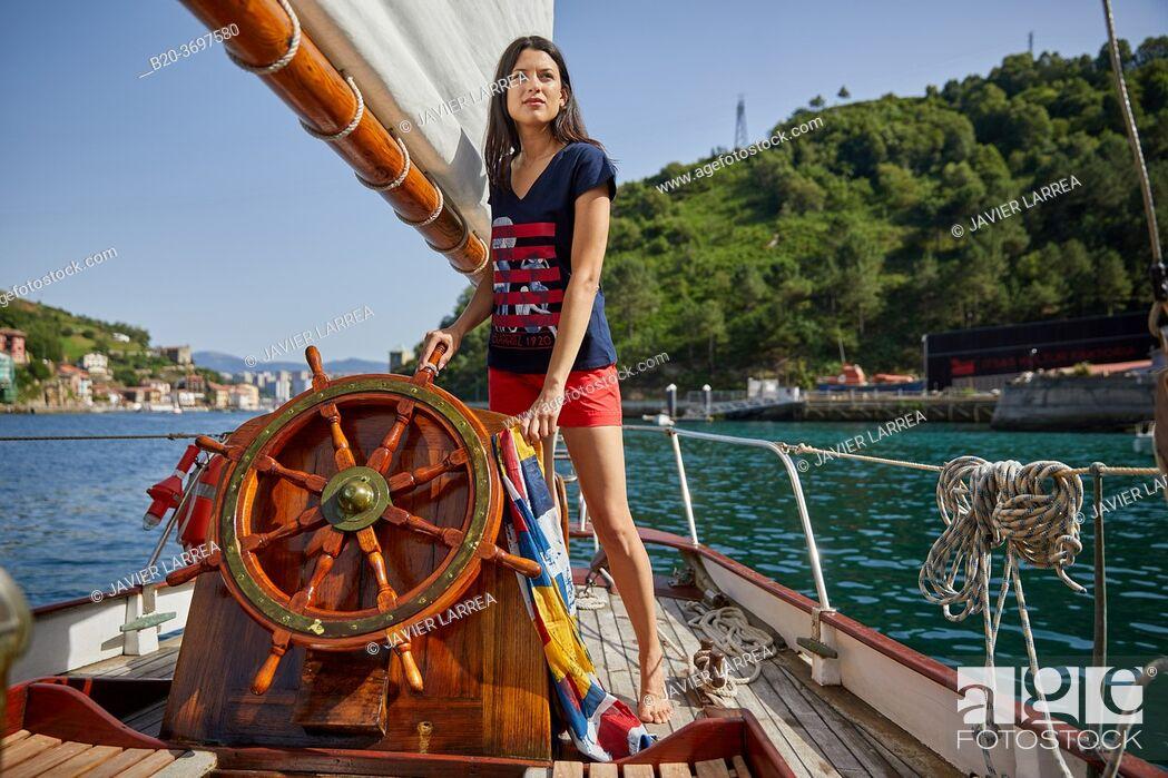 Imagen: Young woman with sailor clothes, Helm, Sailboat, Pasaia, Gipuzkoa, Basque Country, Spain, Europe.