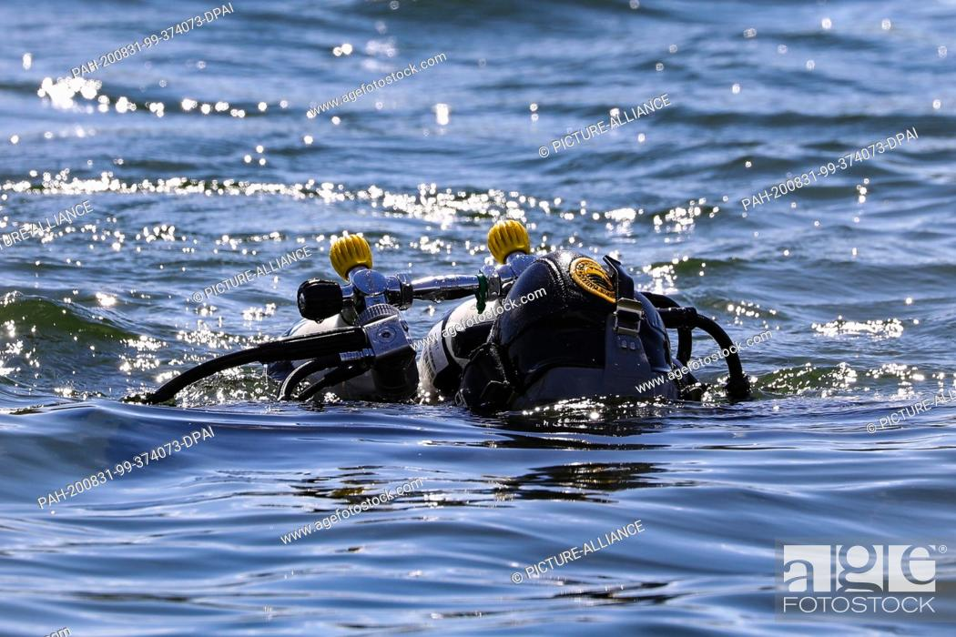 Stock Photo: 28 August 2020, Saxony, Dresden: Diver with wetsuit and oxygen tanks on the back just before the dive Photo: Tino Plunert/dpa-Zentralbild/ZB.