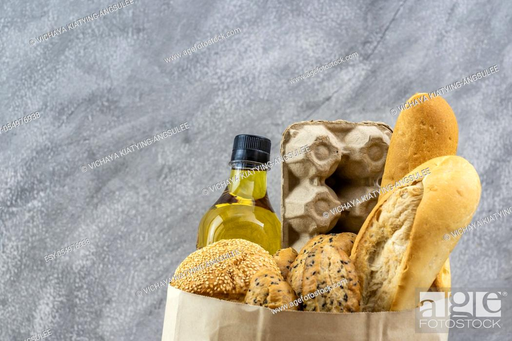 Stock Photo: Grocery bag with egg cooking oil and variety of bread in disposalable paper bag on gray vintage loft background. Bakery food and drink and grocery concept for.