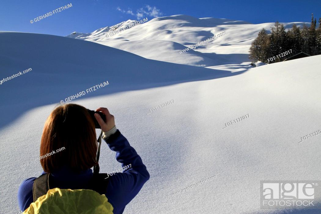 Stock Photo: Tourist takes photos of snowy landscape.