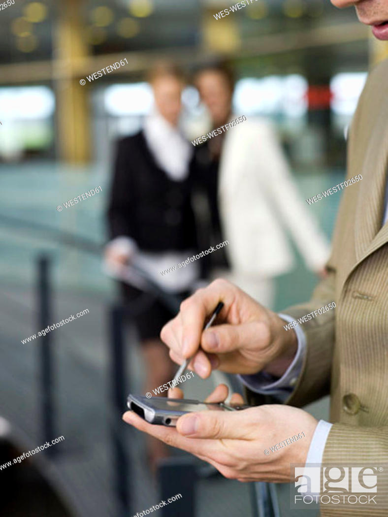 Stock Photo: Young businessman using mobile phone, women talking in background.