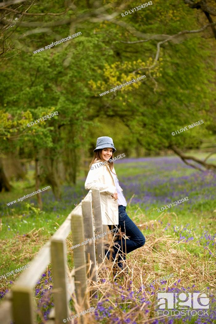 Stock Photo: A young woman leaning against a fence in the countryside, smiling.