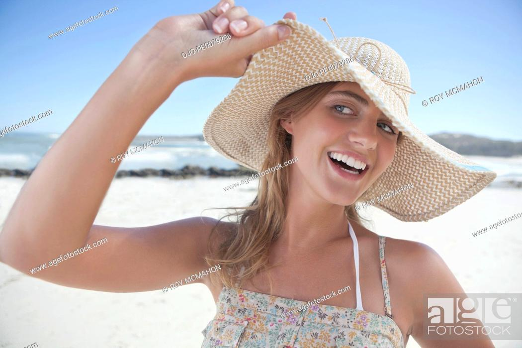 Stock Photo: Smiling woman standing on beach.