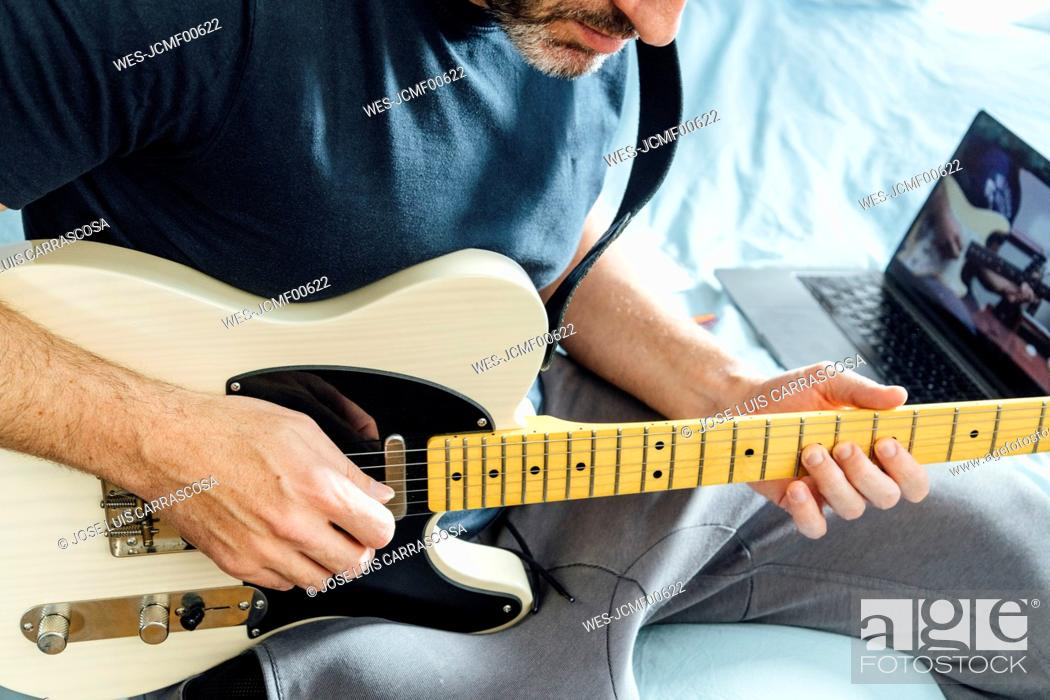 Imagen: Man learning to play electric guitar online using laptop.