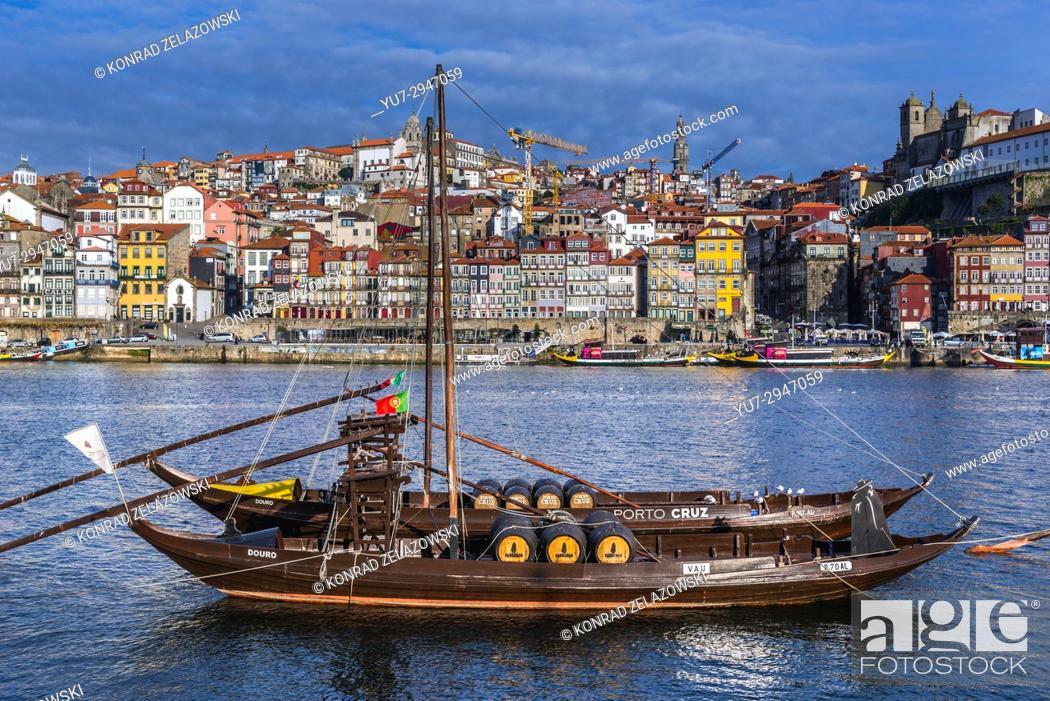 Stock Photo: Sandeman and Porto Cruz Port wine boats called Rabelo Boats on a Douro River in Vila Nova de Gaia city. Porto city river bank on background.