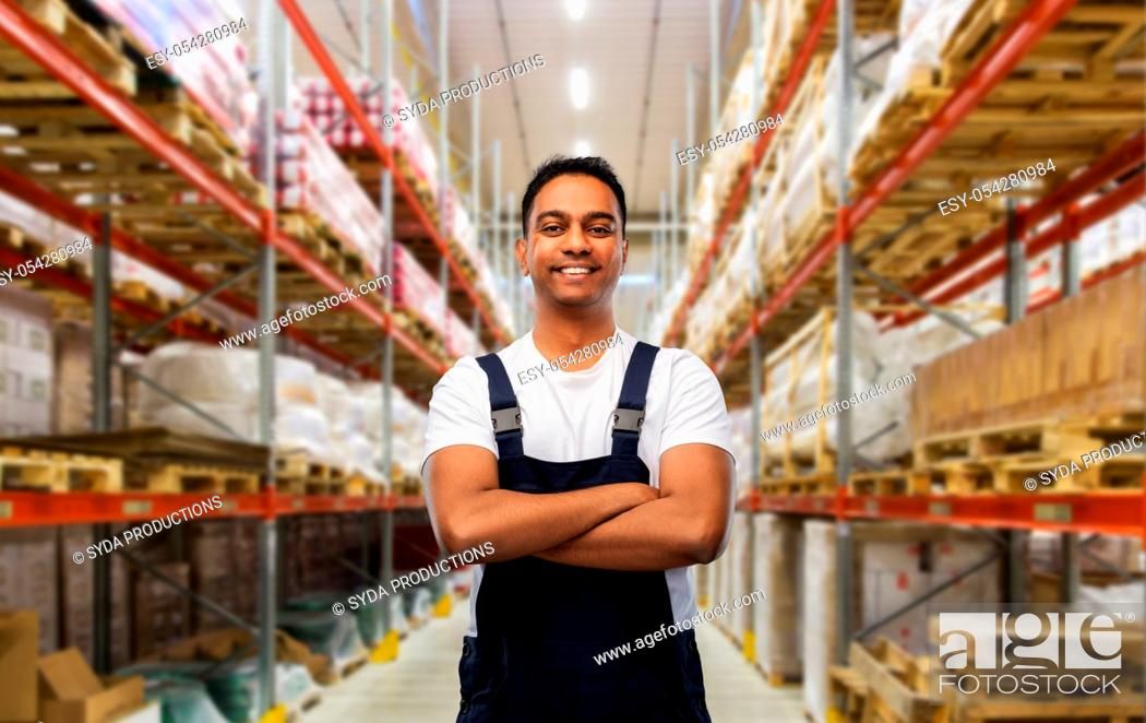 Stock Photo: happy indian worker with crossed arms at warehouse.