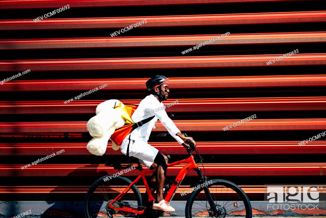 Stock Photo: Bicycle courier delivering a teddy bear passing a red wall.
