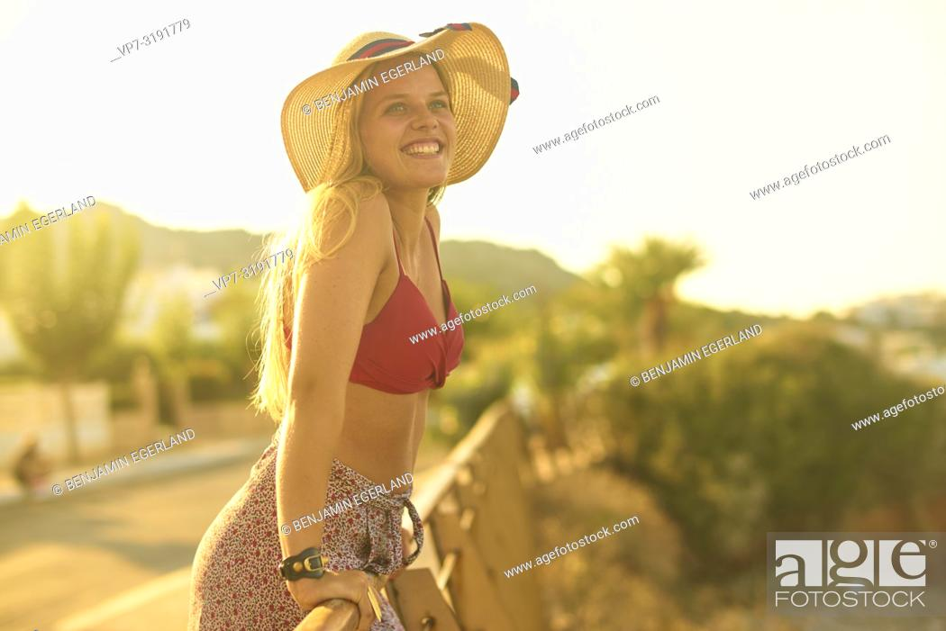 Imagen: Woman leaning on handrailing next to beach, Stalida, Crete, Greece.