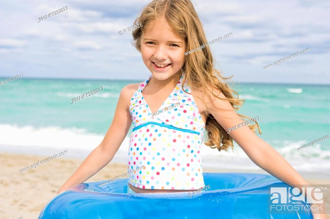 Stock Photo: Girl wearing an inflatable ring on the beach.