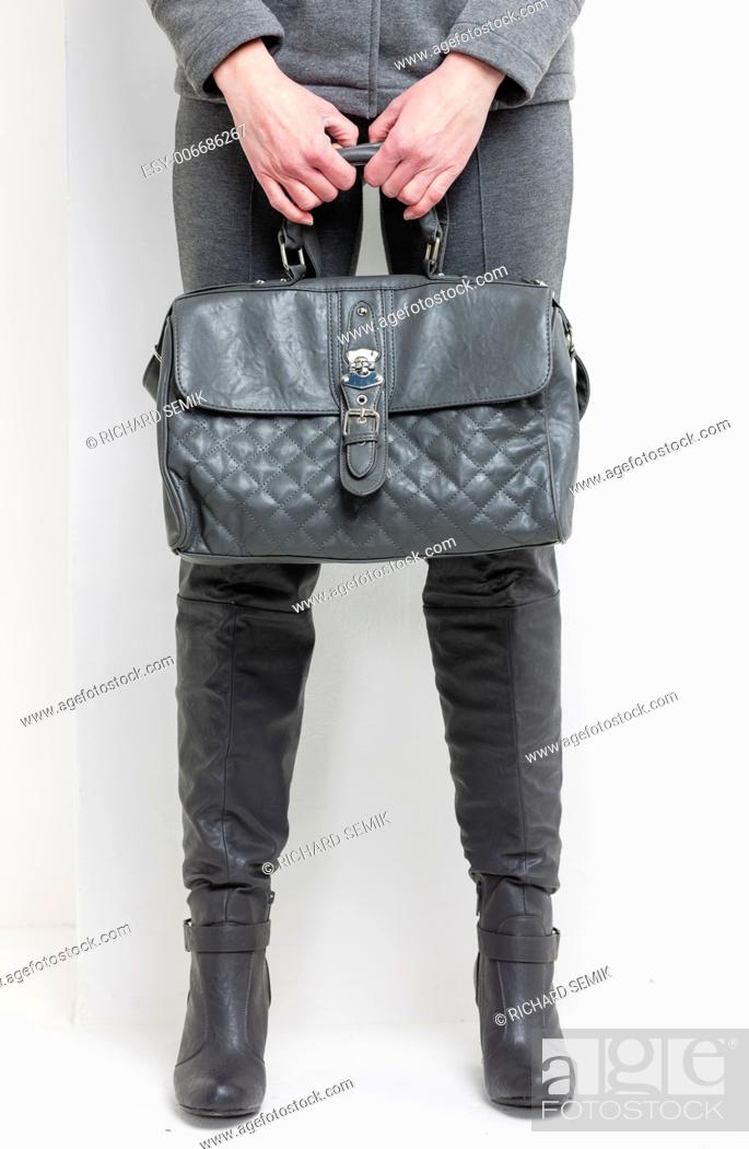 Stock Photo: detail of standing woman wearing grey boots with a handbag.