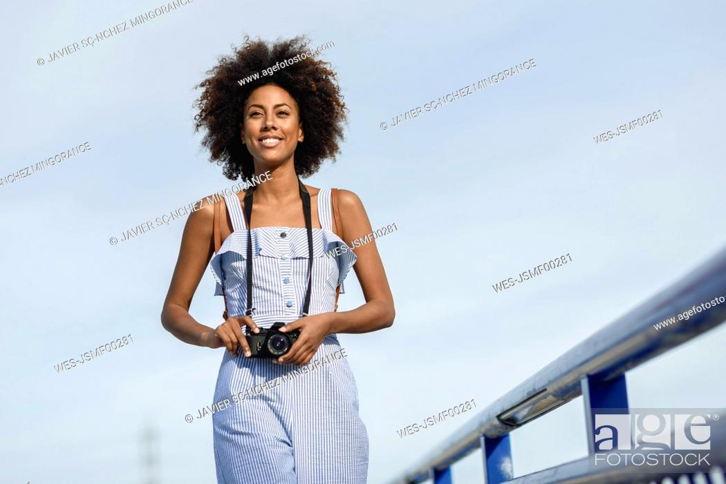 Stock Photo: Portrait of smiling young woman with camera against sky.
