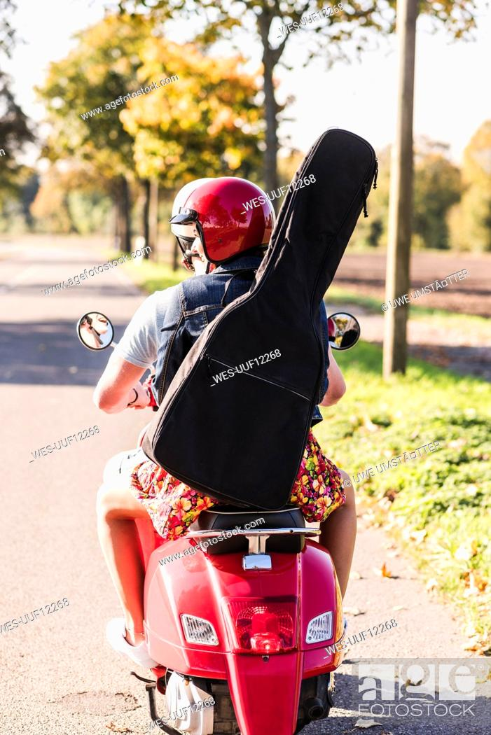 Imagen: Young couple riding motor scooter with guitar bag on the back.