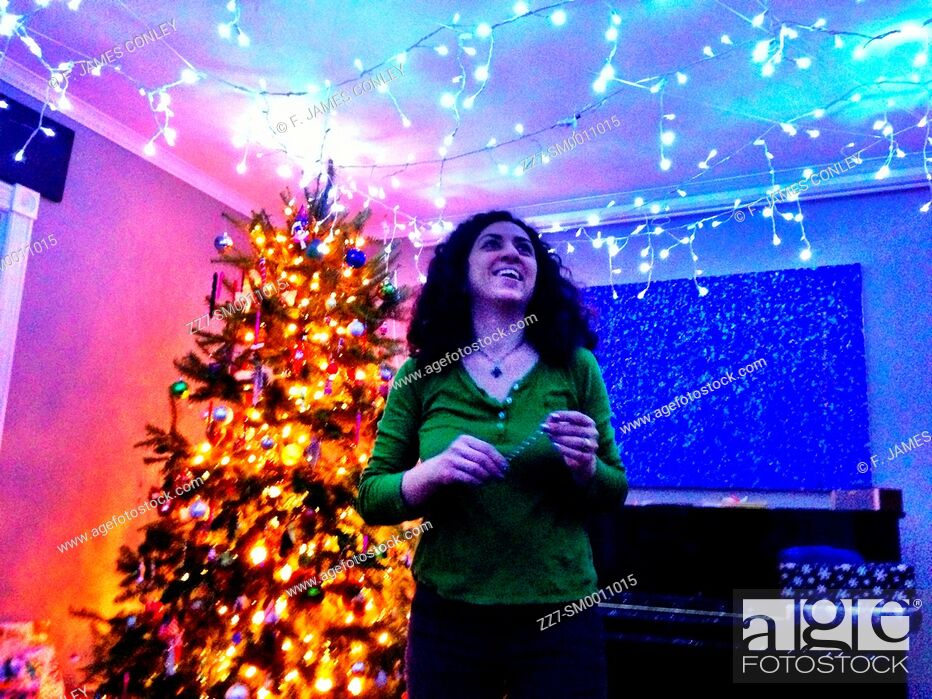 Stock Photo: A woman decorates a room with holiday lights.
