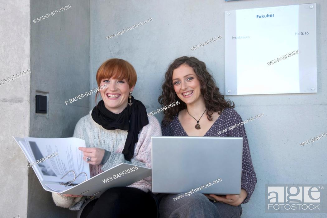 Stock Photo: Germany, Leipzig, University students using laptop, smiling, portrait.