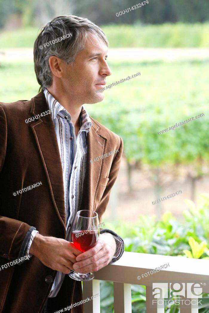 Stock Photo: Mid adult man drinking red wine on patio (portrait).