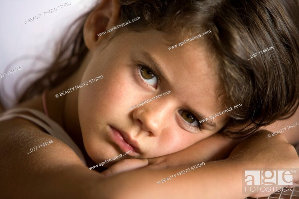 Stock Photo: Little girl looking at the camera with big brown eyes.