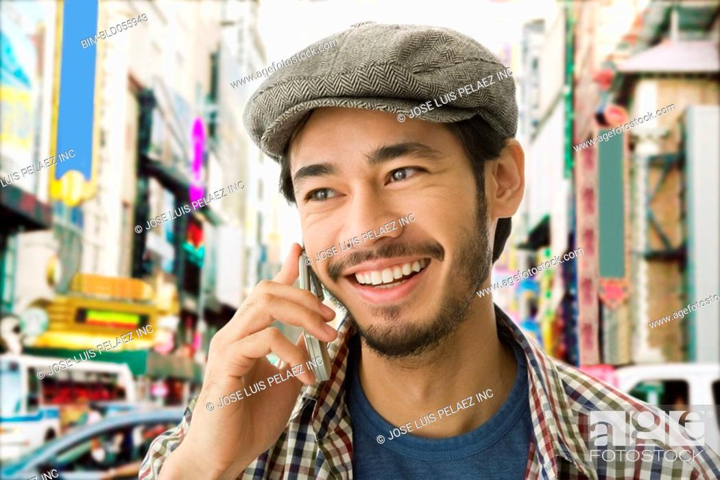 Stock Photo: Asian man talking on cell phone.