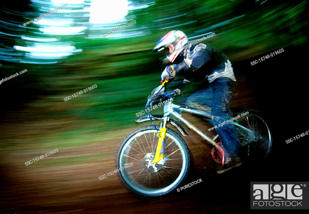 Stock Photo: Side profile of a teenage boy riding a bicycle.