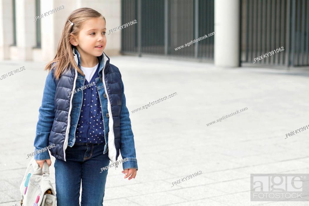 Stock Photo: Schoolgirl carrying her schoolbag.