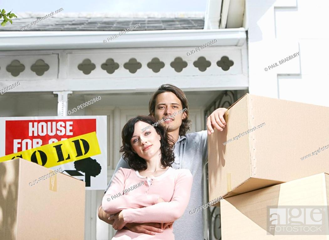 Stock Photo: Man and woman with cardboard boxes standing in front of house with sold sign.